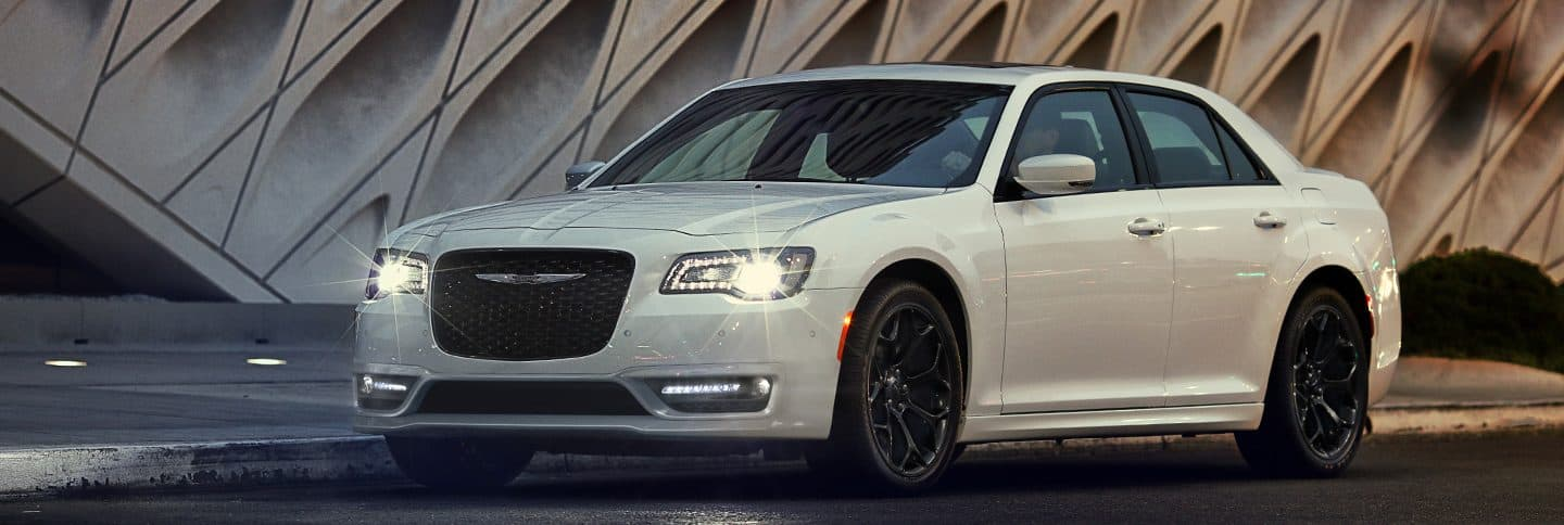 The 2019 Chrysler 300 being driven on a city street with its headlamps on.