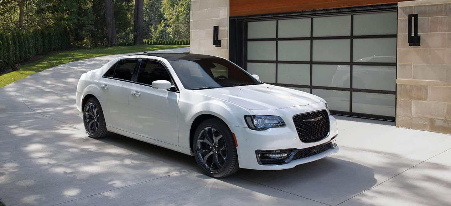 Display A white 2020 Chrysler 300S with both the S Appearance Package and Red S Appearance Package parked next to a garage.