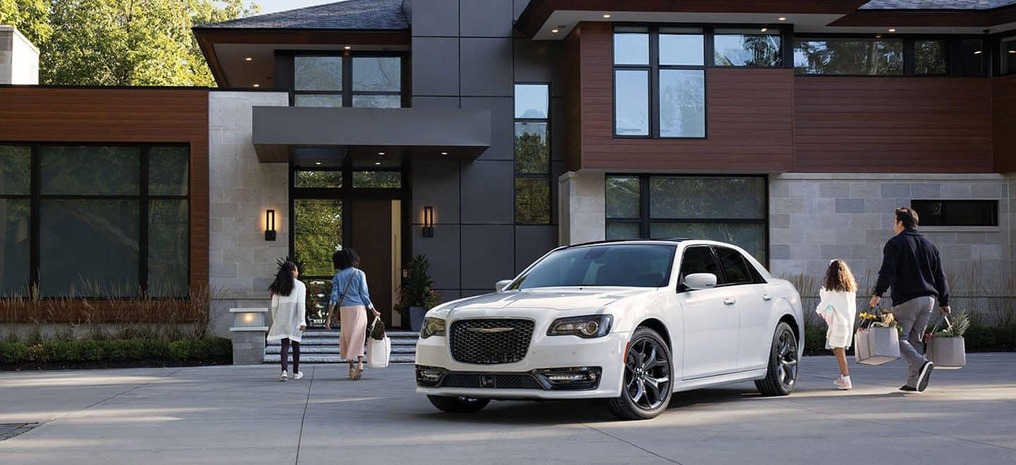 Display A family of four head to a contemporary home after exiting a 2020 Chrysler 300S with both the S Appearance Package and Red S Appearance Package.