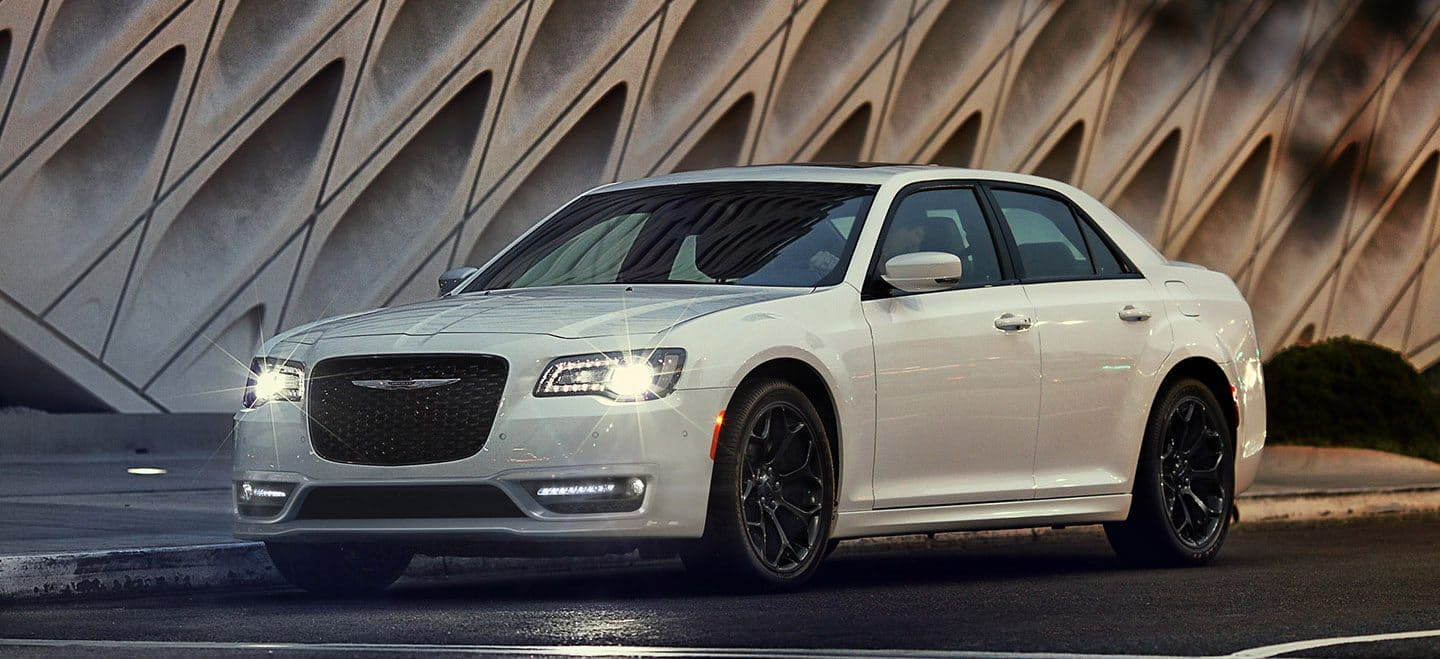 Display The 2020 Chrysler 300S parked next to a commercial building in the evening with its headlamps on.