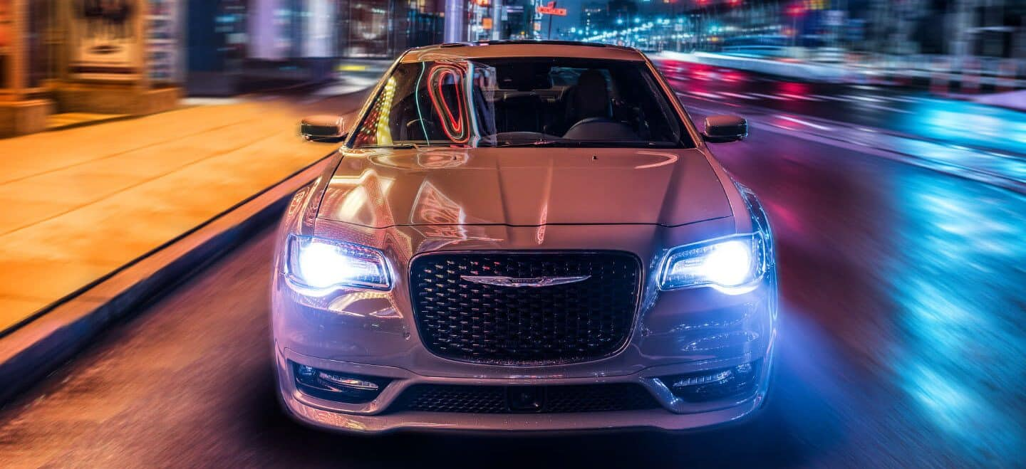 Display A front view of the 2020 Chrysler 300S being driven on a city street at night with its headlamps on.
