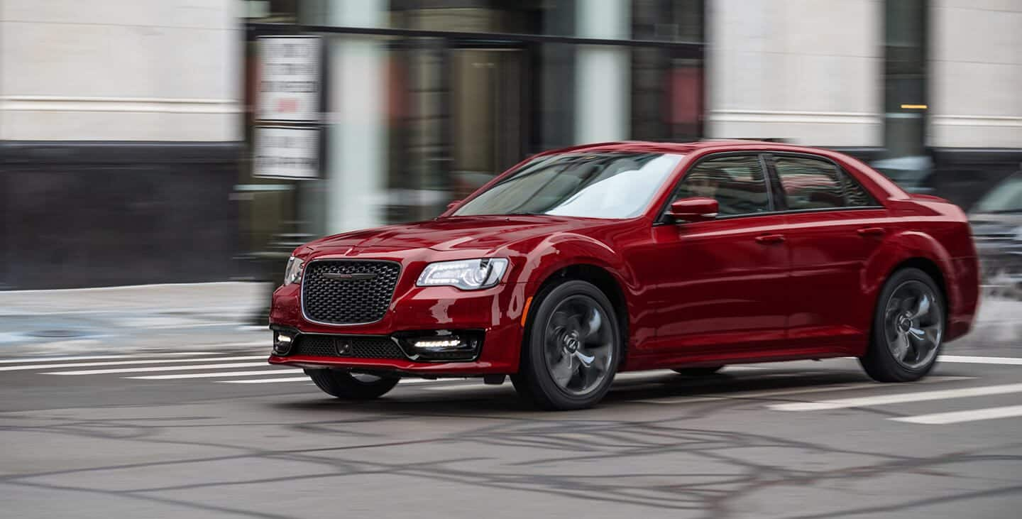 The 2021 Chrysler 300S V8 in Velvet Red, with the Sport Appearance Package, being driven on a city street.