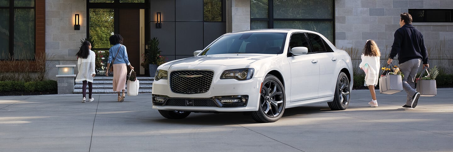 The 2021 Chrysler 300S V8 parked in front of a house with a family walking toward the front door.