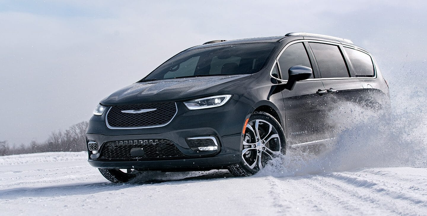 Display The 2021 Chrysler Pacifica Pinnacle being driven on snow.