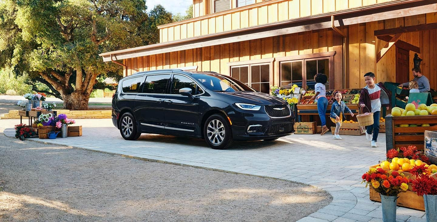 Display The 2021 Chrysler Pacifica Hybrid Pinnacle parked in front of an farmers market with a family of five shopping for produce.