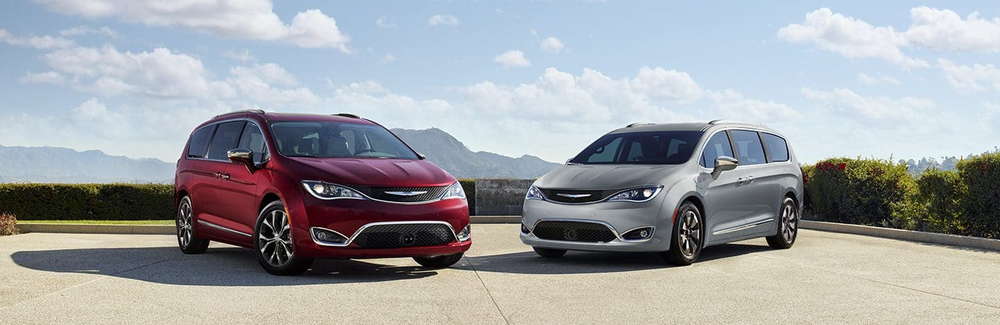 Front view of the Chrysler Pacifica in Red and the Chrysler Pacifica Hybrid in Silver parked and angled toward one another.