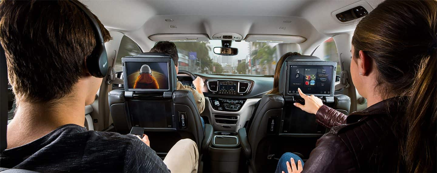 Two people using the Uconnect Theater in the second row of their vehicle.
