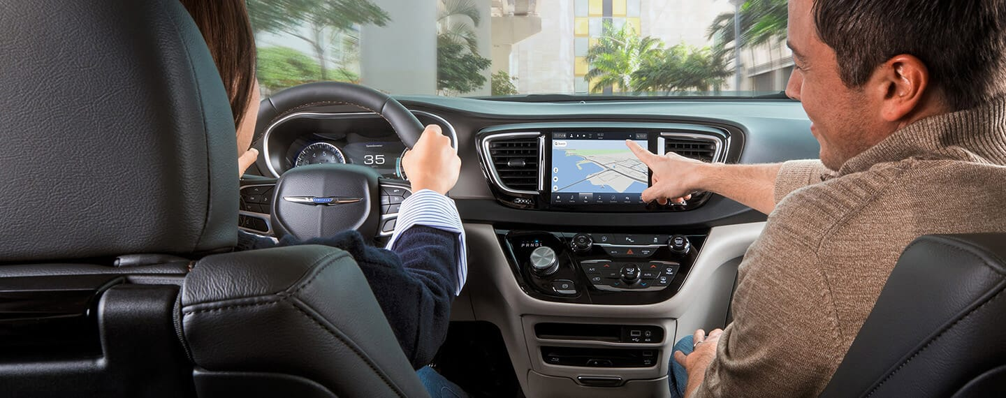 The front passenger in a 2021 Chrysler Pacifica Limited reaching for the vehicle's touchscreen, on which a route map is displayed as the driver keeps his hands on the wheel.
